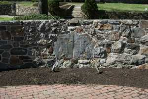 a stone wall that contains to larger stones in the middle with an engraved message