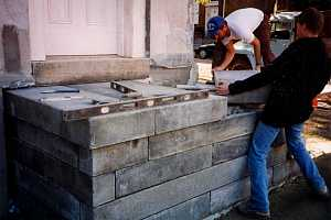 two men installing large stone blocks for steps