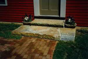 two stone steps leading down from a door to a brick walkway - after