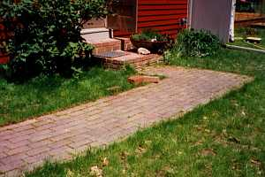 a brick walkway leading to brick steps and a front door - before