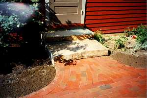 a brick walkway leading to new stone steps and a front door - after