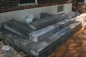 concrete steps being installed in front of a brick home