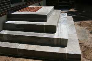 completed concrete steps leading up to a brick landing and front door