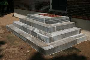 concrete steps leading up to a brick landing and front door