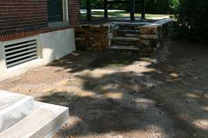 stepping stones leading from concrete stairs to natural stone steps and wall