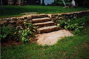 natural stone steps in between a natural stone retaining wall