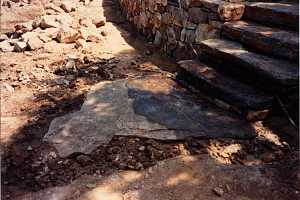 a natural flagstone landing beneath stone steps