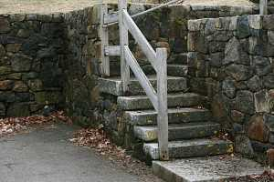 stone retaining wall and natural stone steps leading to higher ground