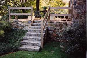 a stone wall and with stone steps leading up to a stone patio. a wood railing leads you up it.