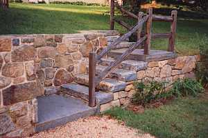 stone steps leading up to a landing, then leading up to a back yard. a wood railing leads you up it.