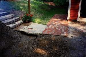 a brick walkway leading out of a home. stone steps run down a hill into a stone landing that connects to the brick walkway