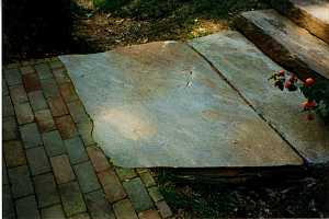 a closeup of the stone landing that connects to a brick walkway