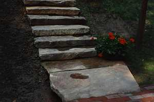 a brick walkway leading to stone stairs that take you up to a home on higher ground