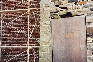 a cracked stone wall with scaffolding next to it