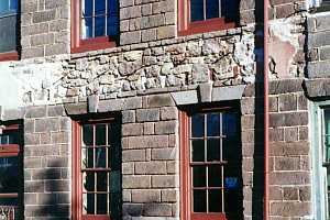 a repaired stone wall between two sets of windows on a stone building