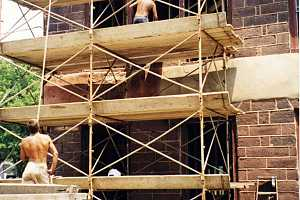 men on scaffolding repairing a damaged stone building