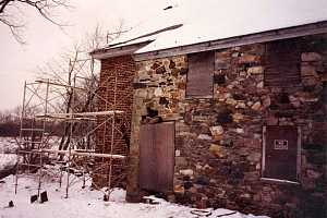 an old stone and brick building with boarded windows and cracked stone