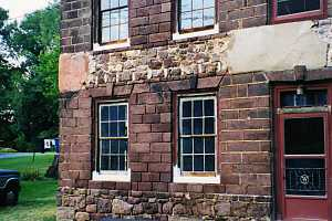 a repaired stone wall section on a stone home