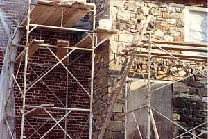 a man standing on scaffolding repairing a stone wall