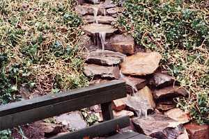 a stone waterfall behind a bench