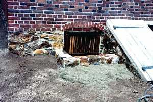 a stone window well next to a cellar door