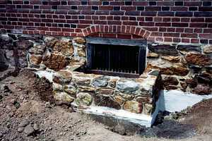 a newly installed natural stone window well with the area around it dug out