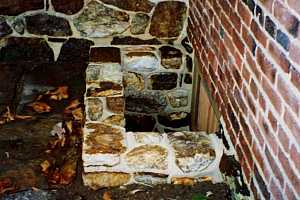 a newly installed natural stone window well at the corner of a stone and brick building