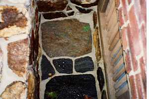 looking down in a natural stone window well with a drain in the middle